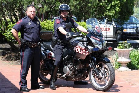 Police officer on motorcycle with police chief standing next to him